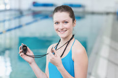 Pretty trainer blowing whistle and looking at stopwatch Royalty Free Stock Photo