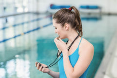 Pretty trainer blowing whistle and looking at stopwatch Royalty Free Stock Images