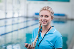 Pretty trainer holding a stopwatch. At the pool royalty free stock photos