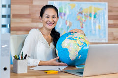 Pretty travel agent holding globe and smiling at camera Royalty Free Stock Image