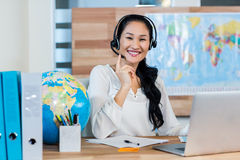 Pretty travel agent smiling at camera. In the office Stock Image