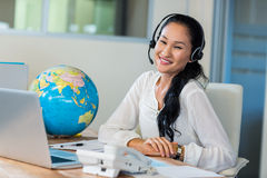 Pretty travel agent smiling at camera. In the office Royalty Free Stock Image