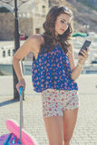 Pretty traveler girl with pink suitcase and cellphone Royalty Free Stock Photography