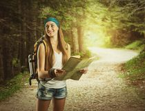 Pretty traveler woman with backpack. Hiking girl with backpack in the forest is holding a map Stock Photo