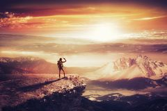 Pretty traveler woman with backpack. On the top of mountain looking at sunset Stock Photo