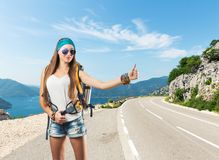 Pretty traveler woman is catching a car. Pretty traveler woman with backpack is catching a car on the road Royalty Free Stock Image