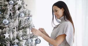 Pretty trendy woman decorating an Xmas tree Stock Images