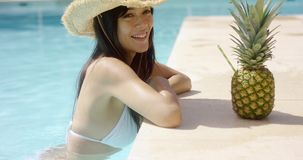 Pretty trendy young woman in a summer pool. At a tropical resort leaning on the tiled surround in a sunhat smiling at the camera with a fruity cocktail in a stock footage