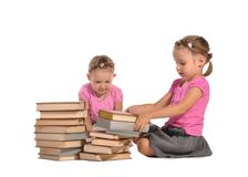 Pretty twins girls with pile of books isolated Stock Images