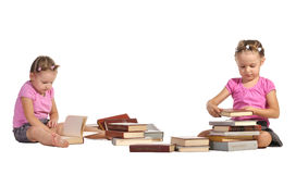 Pretty twins girls with pile of books isolated Stock Photos