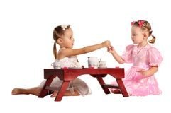 Pretty twins sisters have tea isolated Royalty Free Stock Image