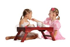 Pretty twins sisters have tea isolated Stock Photos