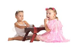 Pretty twins sisters have tea isolated Royalty Free Stock Photography