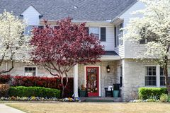 Pretty two story house with rock bottom and white frame with shutters on top in springtime with pansies and flowering trees and stock photography