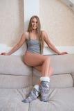 Pretty underwear model sitting on back of sofa Stock Photos