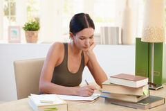 Pretty university girl studying at home Stock Image