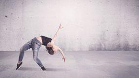 Pretty urban dancer with empty background. A beautiful young hip hop dancer dancing contemporary urban street dance in empty clear grey wall background concept Royalty Free Stock Photo