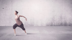 Pretty urban dancer with empty background. A beautiful young hip hop dancer dancing contemporary urban street dance in empty clear grey wall background concept Stock Images