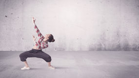 Pretty urban dancer with empty background. A beautiful young hip hop dancer dancing contemporary urban street dance in empty clear grey wall background concept Royalty Free Stock Images