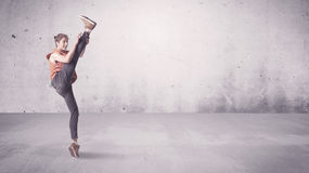 Pretty urban dancer with empty background. A beautiful young hip hop dancer dancing contemporary urban street dance in empty clear grey wall background concept Royalty Free Stock Image