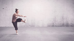 Pretty urban dancer with empty background. A beautiful young hip hop dancer dancing contemporary urban street dance in empty clear grey wall background concept Stock Photos