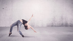 Pretty urban dancer with empty background. A beautiful young hip hop dancer dancing contemporary urban street dance in empty clear grey wall background concept Stock Image