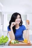 Pretty vegetarian model holds tomato Stock Photo