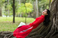 Pretty Vietnamese lady relaxing on tree roots Royalty Free Stock Photography