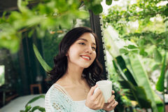 Pretty vietnamese woman enjoying her morning coffee on a veranda Stock Photos