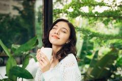Pretty vietnamese woman enjoying her morning coffee on a veranda Royalty Free Stock Images