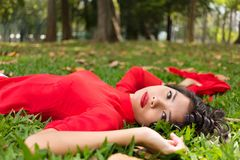 Pretty Vietnamese woman relaxing on the grass Royalty Free Stock Images