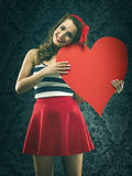 Pretty vintage woman holding a huge heart Royalty Free Stock Photography