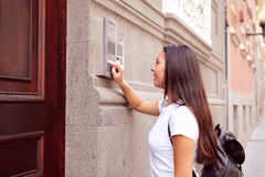 Pretty visiting girl buzzing an intercom Stock Images