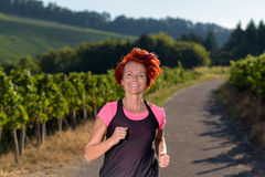 Pretty vivacious redhead woman out jogging Royalty Free Stock Photo