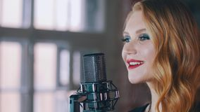 Pretty vocalist with bright make up perform on stage at concert microphone. Jazz stock video footage