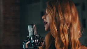 Pretty vocalist with dark lips perform on stage at concert microphone. Jazz stock video footage