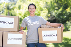 Pretty volunteer holding a donation box in park Stock Photo