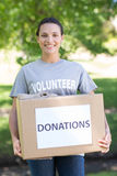 Pretty volunteer holding a donation box in park Royalty Free Stock Images