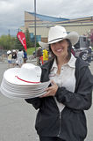 Pretty volunteer with white cowboy hats. A pretty female volunteer smiles as she looks for people to give a free white cowboy hat to at a Calgary Stampede Stock Photography