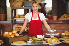 Pretty waitress bended over a food table Stock Photography