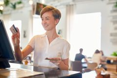Pretty Waitress at Cash Desk. Smiling pretty waitress standing at cash desk and using credit card of visitor in order to pay for his order, interior of spacious Stock Image