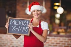 Pretty waitress with a chalkboard merry x-mas Royalty Free Stock Photo