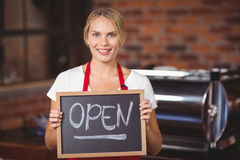 Pretty waitress with a chalkboard open sign Royalty Free Stock Photo