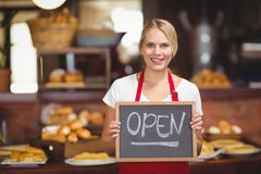 Pretty waitress with a chalkboard open sign Stock Photography