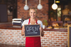 Pretty waitress with a chalkboard open sign Royalty Free Stock Photos