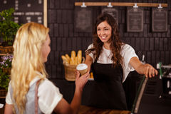 Pretty waitress giving cup of coffee to customer Royalty Free Stock Photos