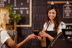 Pretty waitress giving cup of coffee to customer Royalty Free Stock Image