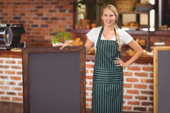 Pretty waitress holding a big chalkboard Stock Photo