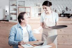 Pretty waitress holding a tray and giving coffee to a visitor. Take it. Cheerful friendly professional waitress looking at the visitor and smiling while giving Royalty Free Stock Photos