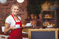 Pretty waitress holding two cups of coffees Royalty Free Stock Photography